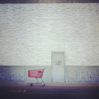 Empty shopping cart on road by building