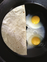 Overhead view of flatbread and fried eggs in pan
