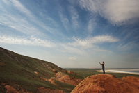 Side view of woman photographing while standing on mountain against sky