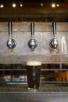Beer glass under taps