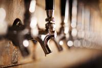 Close-up of metallic beer taps at bar