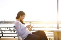 Side view of happy woman using tablet computer at cafe on promenade against clear sky