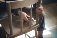 Midsection of female carpenter sanding wooden chair at workshop
