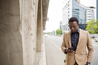 Businessman using smart phone on city street