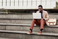 Businessman using laptop while sitting on steps