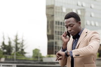 Businessman checking the time while using smart phone in city