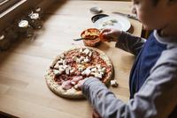 High angle view of boy preparing pizza at home 11100035258| 写真素材・ストックフォト・画像・イラスト素材|アマナイメージズ