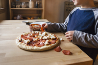 Midsection of boy preparing pizza at home 11100035259| 写真素材・ストックフォト・画像・イラスト素材|アマナイメージズ