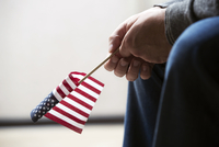 Cropped image of person holding American flag