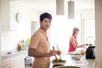 Portrait of man preparing salad with woman standing in background at kitchen
