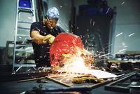 Craftsman cutting metal bar with circular saw at factory