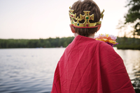 Rear view of boy wearing king costume by river against clear sky