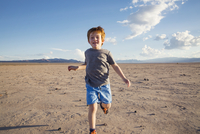 Portrait of happy boy running on arid landscape