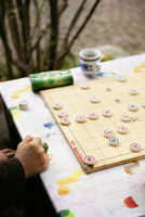 Cropped image of man playing board game outdoors