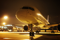 Close-up of airplane at airport during night