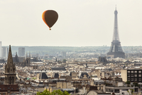 Hot air balloon flying over cityscape with Eiffel Tower in background