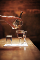 Cropped image of hand pouring cocktail in drink through colander