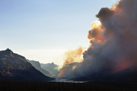 Smoke emitting from Glacier National Park during sunset against clear sky