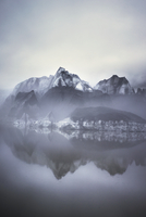 Scenic view of mountain by lake in foggy weather