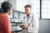 Male doctor writing in note pad while discussing with female patient in clinic 11100035983| 写真素材・ストックフォト・画像・イラスト素材|アマナイメージズ