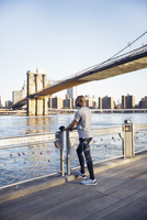 Full length of male athlete standing on promenade with Brooklyn Bridge in background