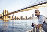 Side view of thoughtful male athlete standing on promenade with Brooklyn Bridge in background