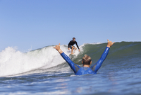 Man cheering while looking at friend surfing on sea against clear blue sky