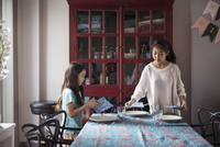 Sisters arranging dining table at home for surprise birthday celebration