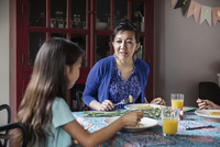 Mother talking to daughter while eating breakfast on birthday