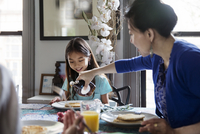 Mother pouring maple syrup on pancakes for daughter during breakfast
