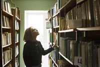 Side view of woman choosing books while standing in library
