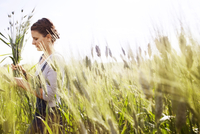 Side view of female farmer holding wheat plants on field 11100036399| 写真素材・ストックフォト・画像・イラスト素材|アマナイメージズ