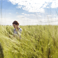Woman in cultivated wheat field against clear sky 11100036400| 写真素材・ストックフォト・画像・イラスト素材|アマナイメージズ