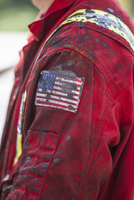 Side view of male worker wearing messy jacket with American flag on sleeve