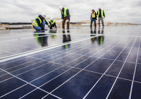 Workers working on solar panel field against cloudy sky