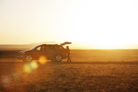 Side view of hiker standing by car on field against clear sky during sunset