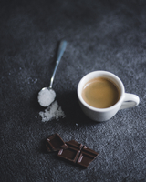 Chocolate bar with coffee cup and sugar on black table