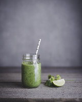 Green smoothie in mason jar with lime on table