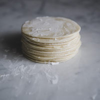 Stack of flat dough on kitchen counter