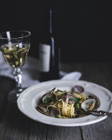 Vongole bianco served in plate and wine on table