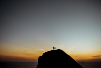 Distant view of couple standing on silhouette cliff against sky by sea during sunset
