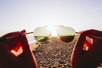 Cropped image of person holding sunglasses on beach during summer