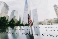American flag on memorial with One World Trade Center in background