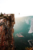 Distant view of person walking on rope tied to cliff at Yosemite National Park