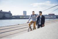 Happy man on bicycle besides friend walking against sky