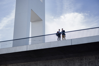 Low angle view of men standing on bridge against sky