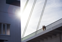 Low angle view of men standing on bridge by building against clear sky