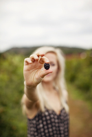 Young woman holding fresh blackberry on field against sky 11100036908| 写真素材・ストックフォト・画像・イラスト素材|アマナイメージズ