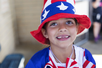 Portrait of cute girl wearing American Flag hat outdoors
