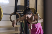 Tired female athlete leaning on gymnastic rings in health club